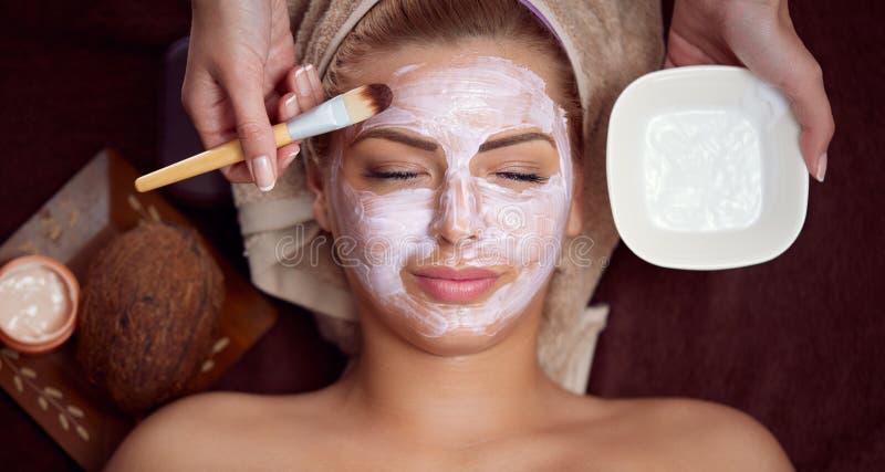 Donna con la mascherina facciale al salone di bellezza immagine stock