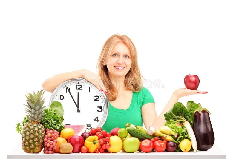 Donna con la mela, orologio e frutta e verdure rossi su una tavola immagini stock libere da diritti