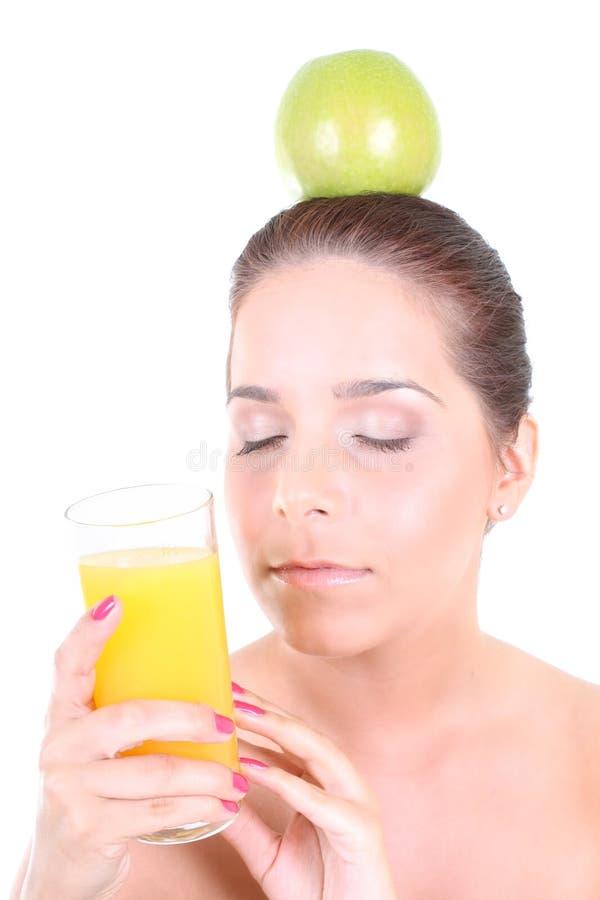 Donna con la mela verde e vetro del succo di arancia immagini stock libere da diritti