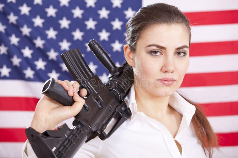 Donna con la mitragliatrice sopra la bandiera americana immagine stock