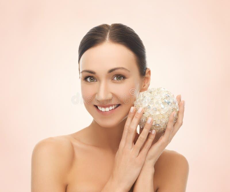 Donna con la palla del sale per bagnare fotografie stock