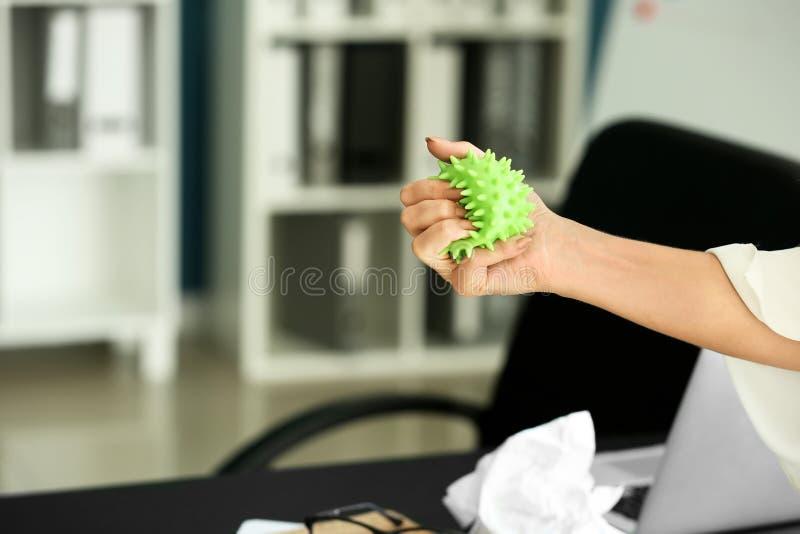 Donna con la palla di sforzo nel luogo di lavoro fotografie stock