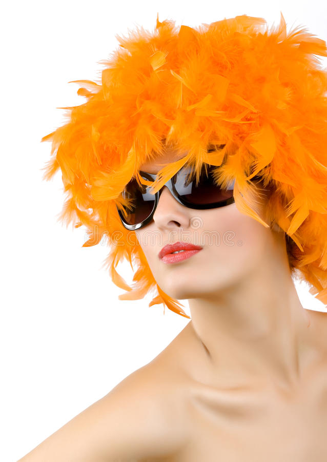Donna con la parrucca e gli occhiali da sole arancioni della piuma fotografie stock libere da diritti