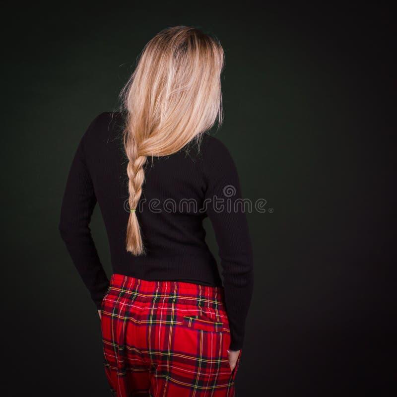 Donna con la pettinatura bionda della treccia e pantaloni scozzesi rossi in un Ca immagine stock