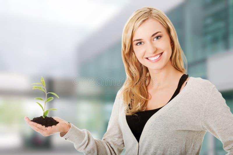 Donna con la pianta ed il suolo a disposizione immagine stock