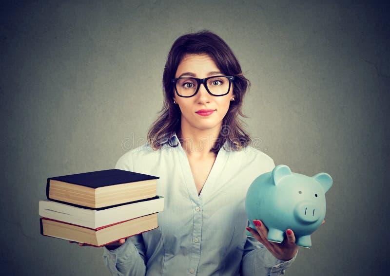Donna con la pila di libri e di porcellino salvadanaio in pieno del debito che ripensa percorso di carriera fotografie stock libere da diritti