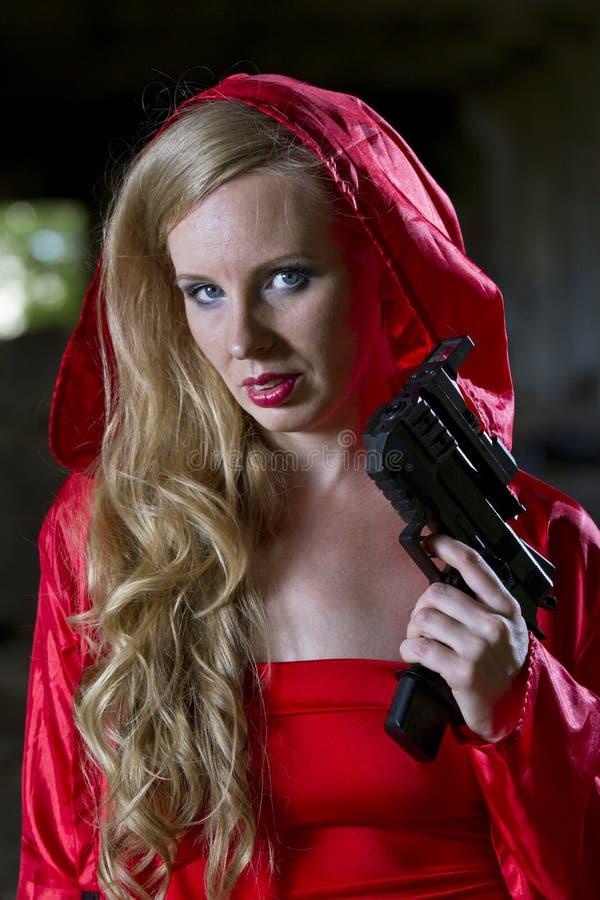 Donna con la pistola in cappotto fotografia stock