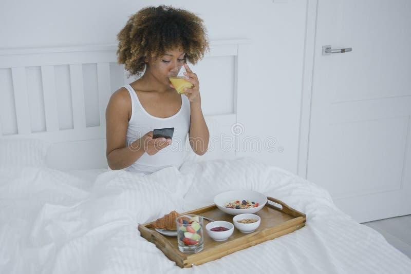 Donna con la prima colazione del enjoyin del telefono a letto fotografia stock