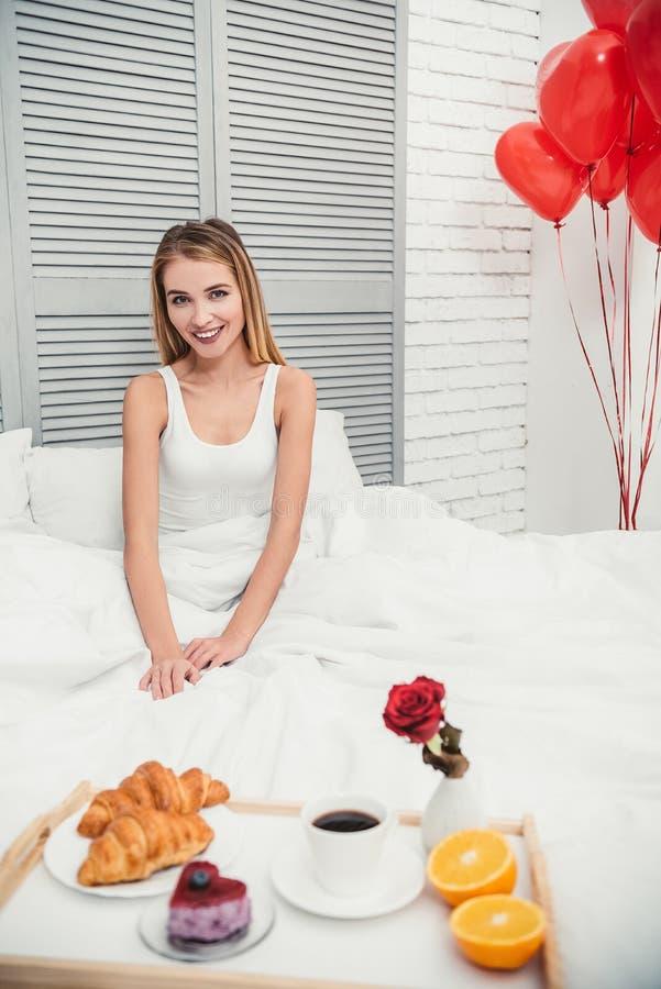 Donna con la prima colazione nel letto immagini stock