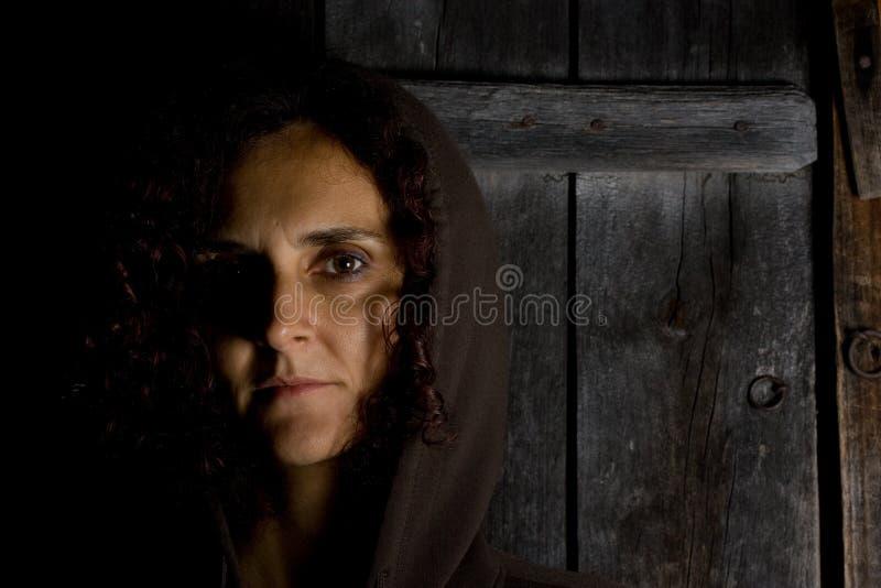 Donna con la protezione con l'espressione nostalgica fotografia stock