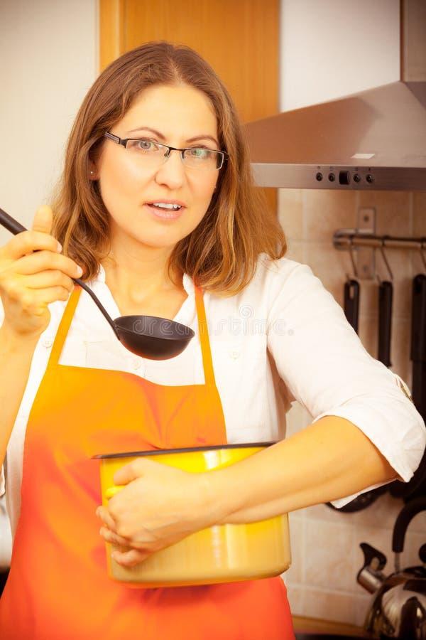Donna con la siviera ed il vaso in cucina immagini stock