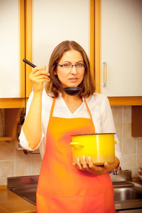 Donna con la siviera ed il vaso in cucina immagine stock