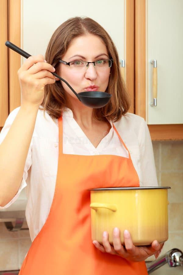Donna con la siviera ed il vaso in cucina fotografie stock libere da diritti