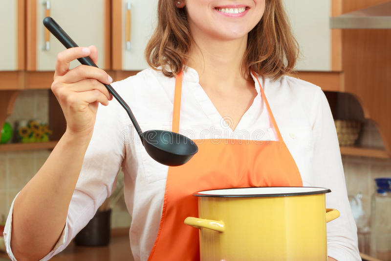 Donna con la siviera ed il vaso in cucina fotografia stock