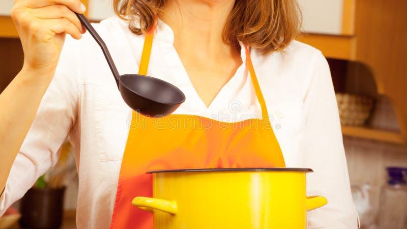 Donna con la siviera ed il vaso in cucina immagine stock libera da diritti