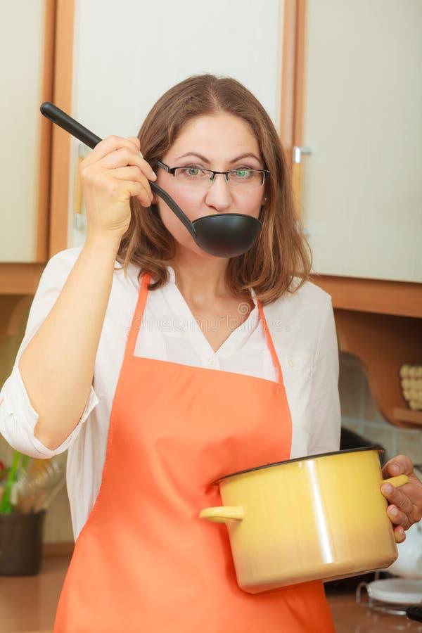 Donna con la siviera ed il vaso in cucina fotografia stock libera da diritti
