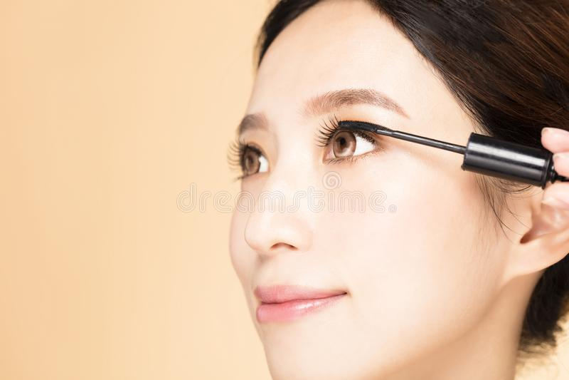 Donna con la spazzola di trucco che applica mascara nera sui cigli immagini stock libere da diritti