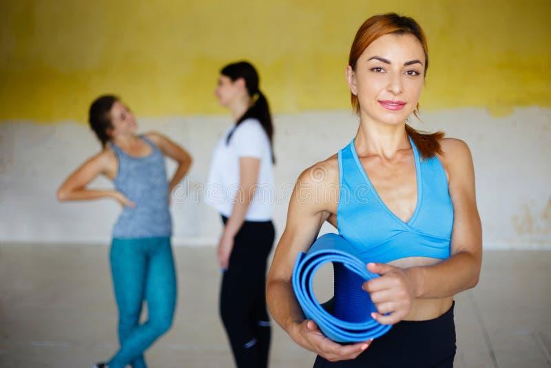 Donna con la stuoia di yoga che posa con gli amici in palestra immagine stock libera da diritti