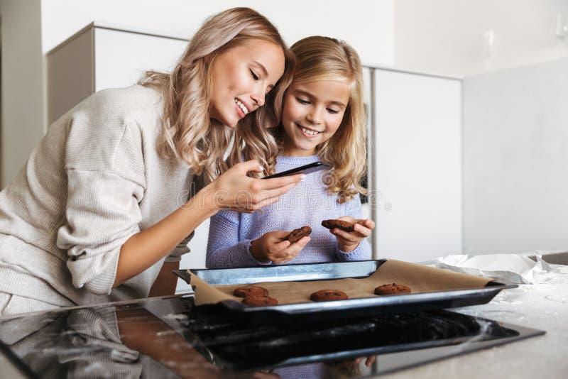 Donna con la sua della sorellina cucina all'interno a casa che cucina il forno di tesori per prendere una foto dal telefono fotografia stock libera da diritti
