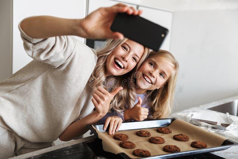 Donna con la sua della sorellina cucina all'interno a casa che cucina il forno di tesori per prendere una foto dal telefono immagine stock