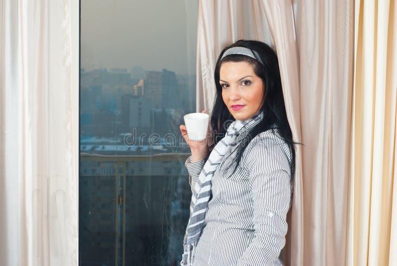 Donna con la tazza davanti alla finestra fotografie stock