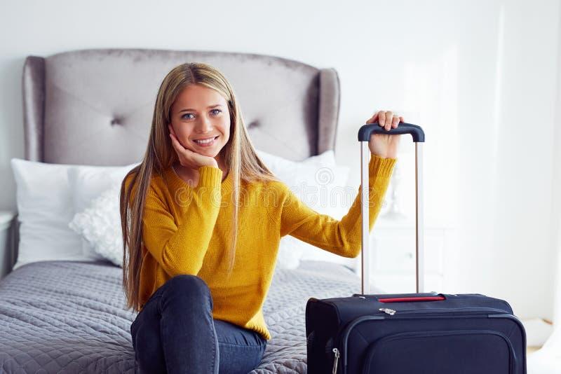 Donna con la valigia che si siede sul letto immagine stock