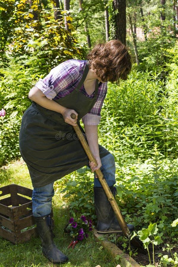Donna con la vanga in un giardino fotografie stock libere da diritti