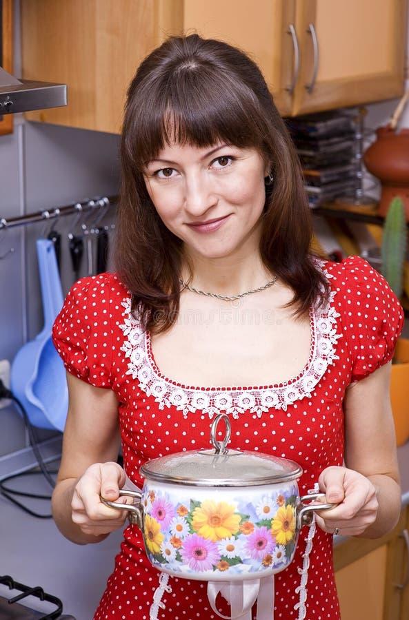 Donna con la vaschetta sulla cucina fotografie stock