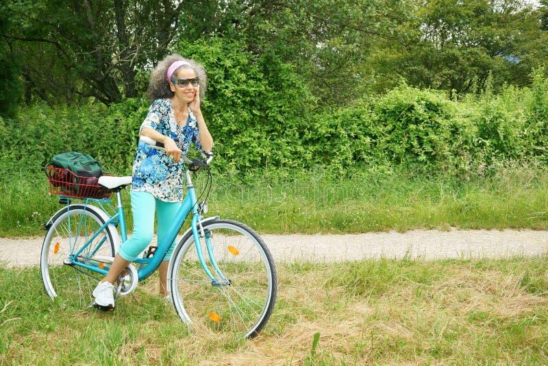 Donna con la vegetazione all'aperto sorridente di verde della natura della bici blu fotografia stock