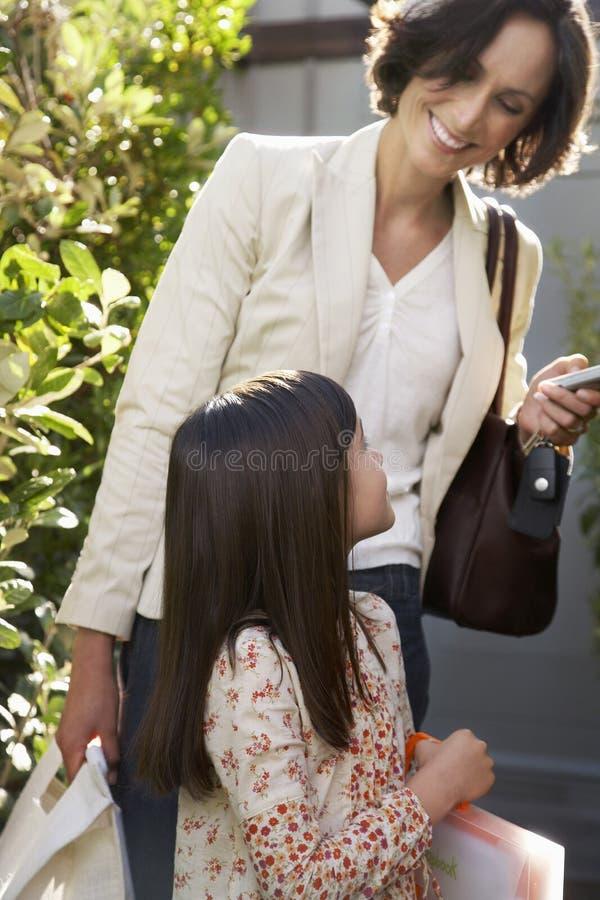 Donna con le borse della tenuta della figlia in Frontyard fotografia stock
