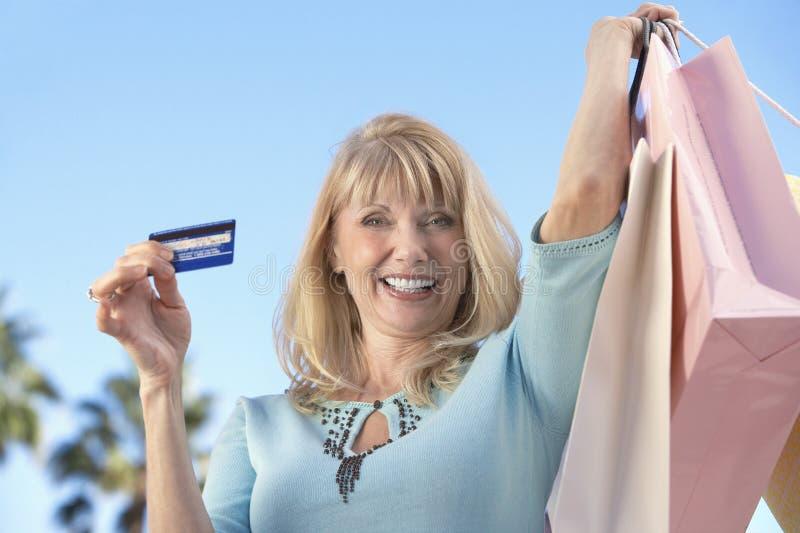 Donna con le borse di acquisto e la carta di credito fotografie stock libere da diritti