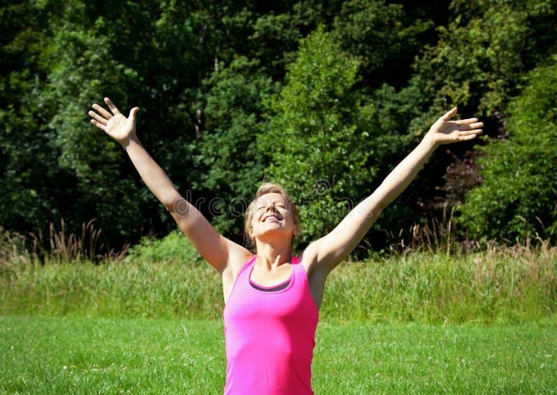 Donna con le braccia alzate fotografie stock