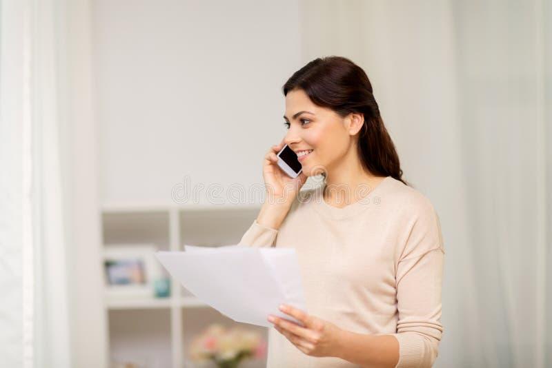 Donna con le carte che rivolge allo smartphone a casa immagine stock libera da diritti