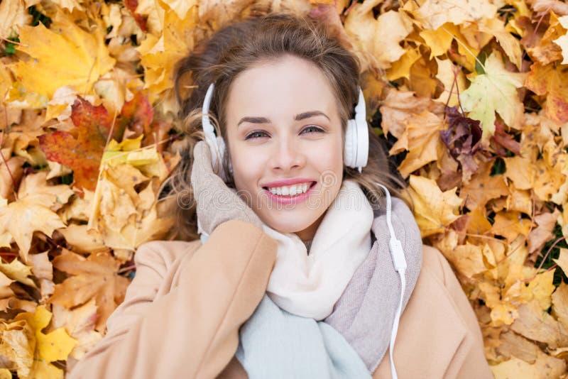 Donna con le cuffie che ascolta la musica in autunno immagine stock