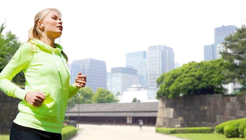 Donna con le cuffie che corre al parco della città fotografia stock