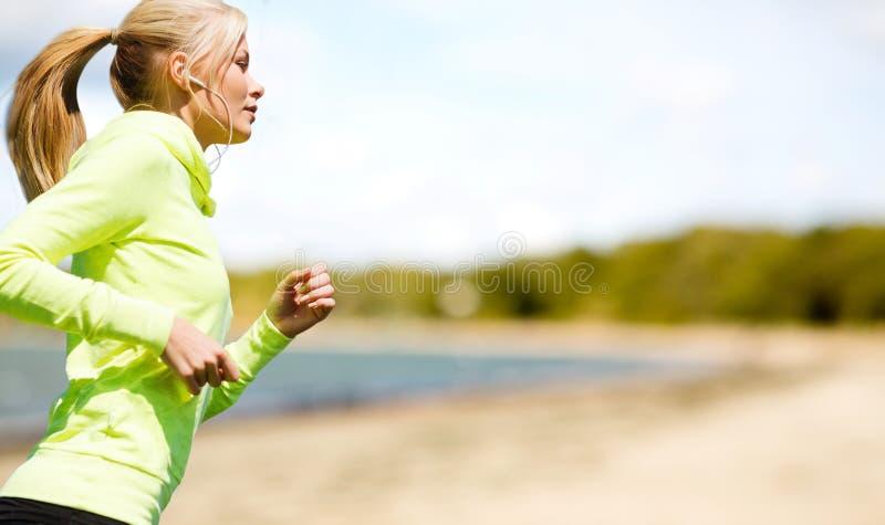 Donna con le cuffie che corre al parco fotografia stock libera da diritti