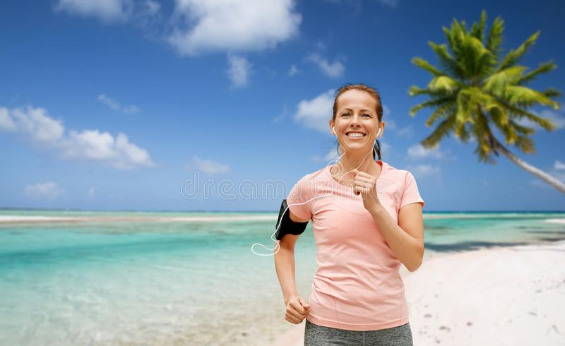 Donna con le cuffie e funzionamento del bracciale sulla spiaggia fotografia stock