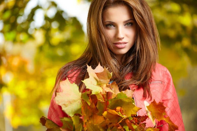 Donna con le foglie di autunno a disposizione ed il luccio giallo dell'acero di caduta immagini stock libere da diritti