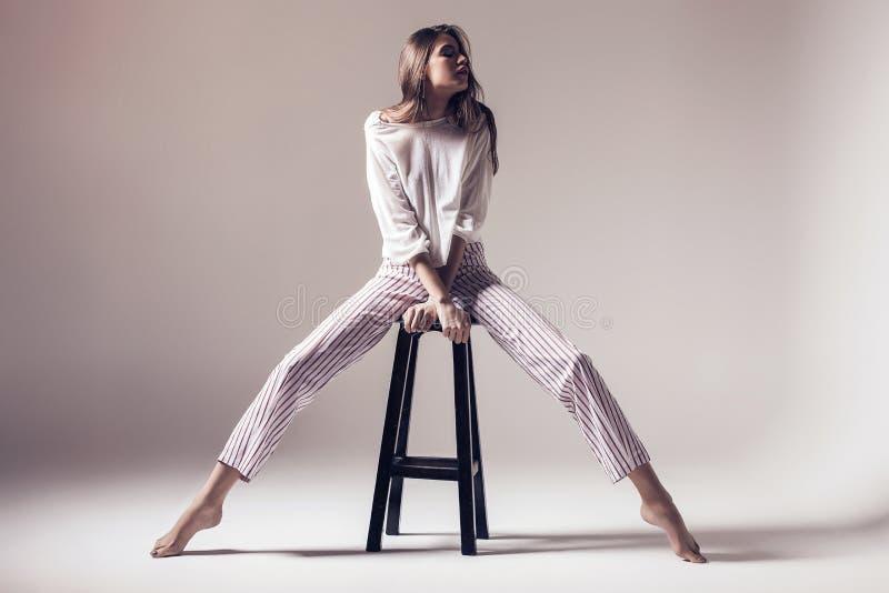 Donna con le gambe lunghe che si siedono sul seggiolone fotografie stock libere da diritti