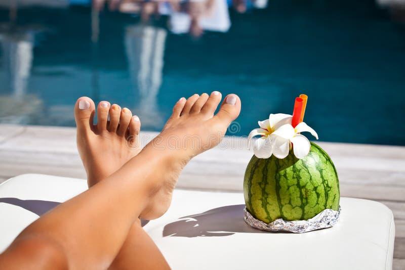 Donna con le gambe lunghe sul poolside fotografia stock