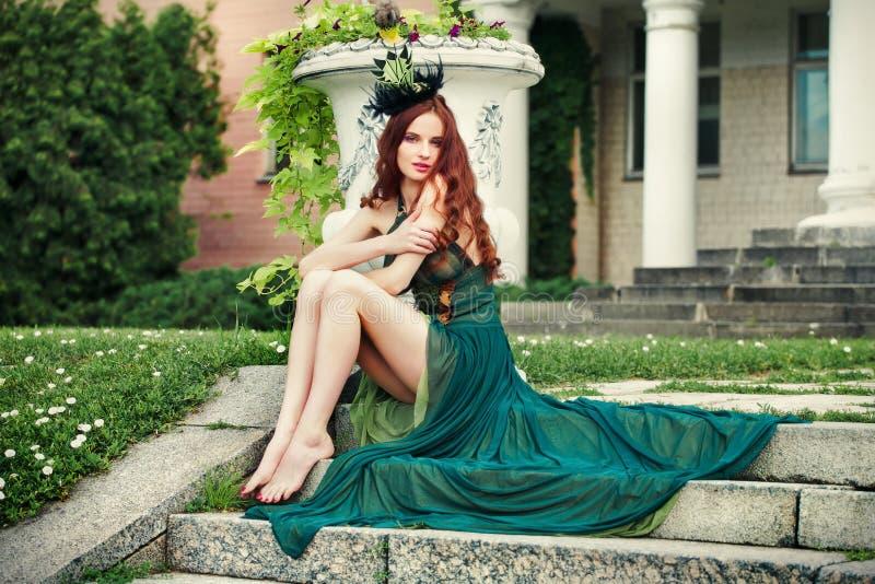 Donna con le gambe lunghe in un vestito verde che si siede sui punti fotografie stock libere da diritti