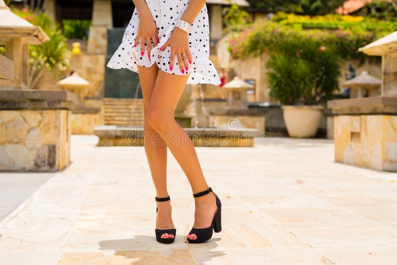 Donna con le gambe sexy esili che posano in vestito bianco da estate e tacchi alti neri immagini stock libere da diritti