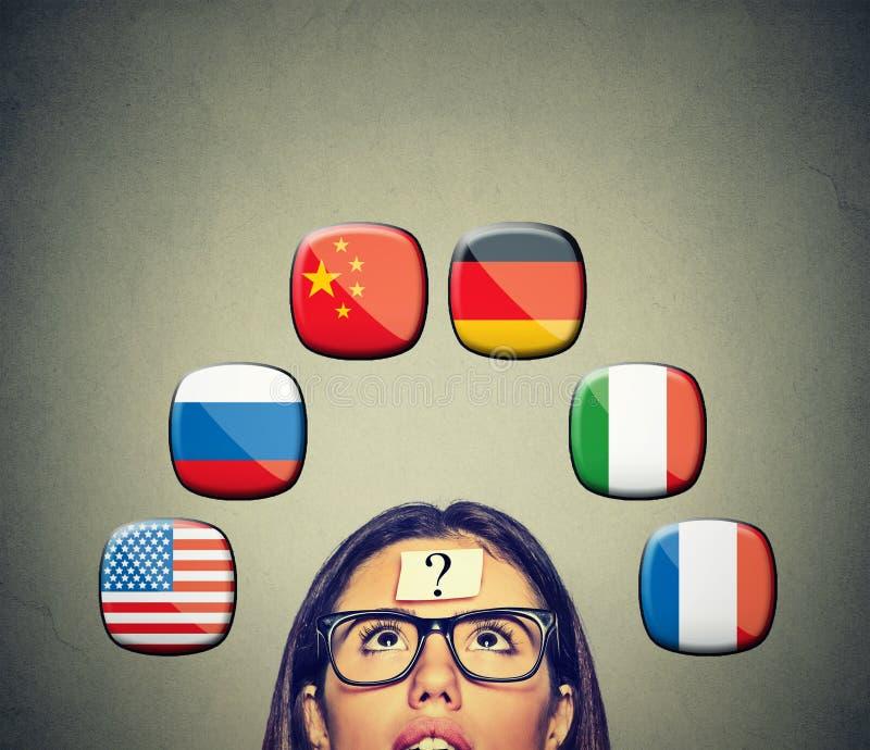 Donna con le icone del punto interrogativo della testa di cui sopra delle bandiere internazionali illustrazione di stock