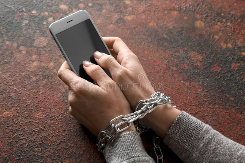 Donna con le mani ed il telefono cellulare incatenati sul fondo di colore Concetto di aggiunta fotografie stock libere da diritti