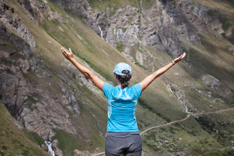 Donna con le parti posteriori a braccia aperte in un paesaggio montagnoso fotografie stock
