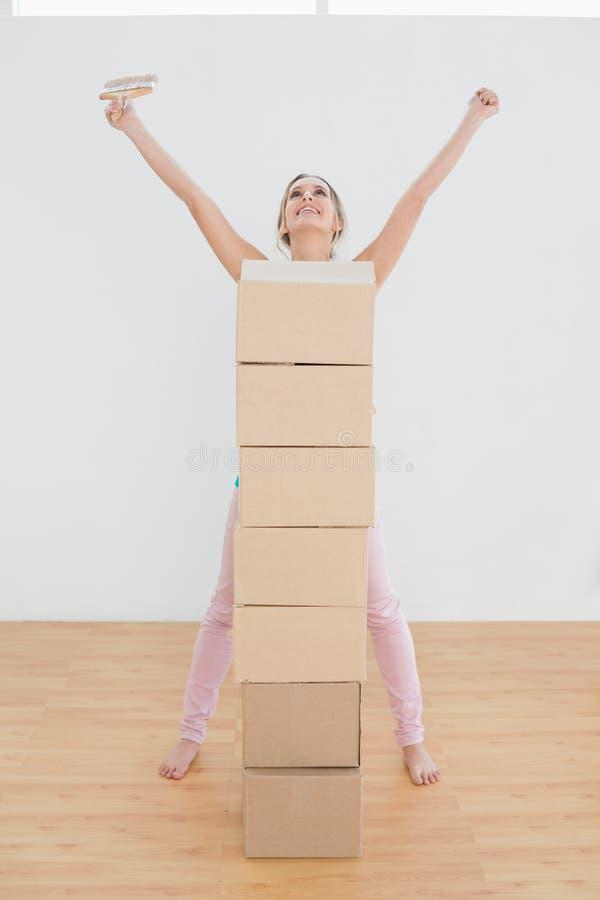Donna con le scatole ed il pennello che sollevano le mani in nuova casa fotografia stock libera da diritti