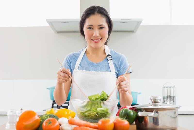Donna con le verdure nella ciotola alla cucina immagini stock