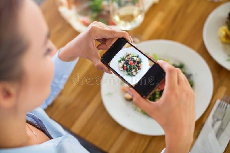 Donna con lo smartphone che fotografa alimento al caffè fotografia stock libera da diritti