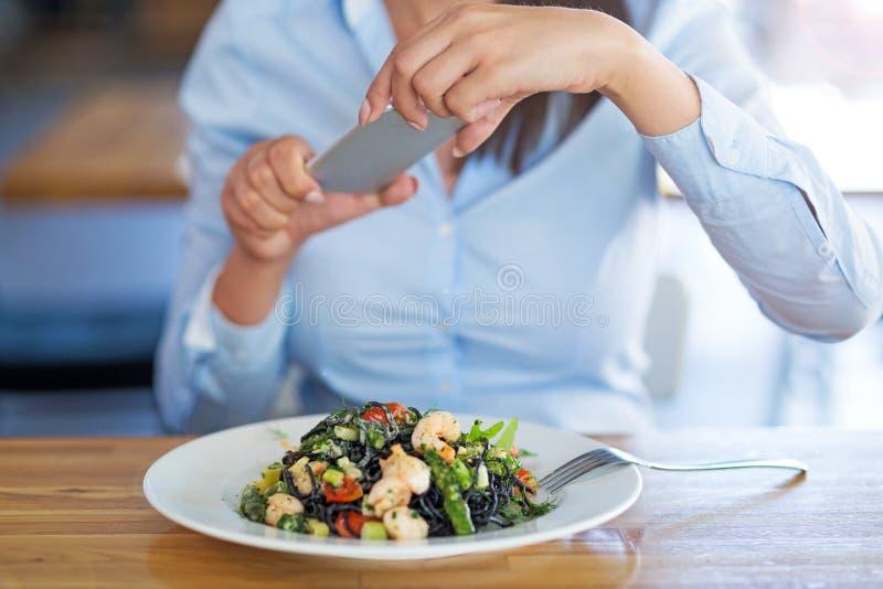 Donna con lo smartphone che fotografa alimento al caffè immagine stock libera da diritti
