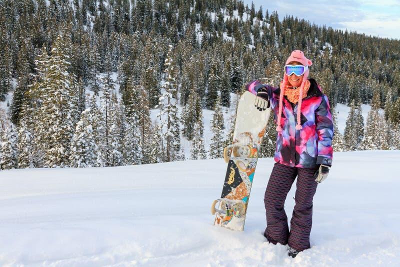 Donna con lo snowboard nella neve fotografia stock libera da diritti